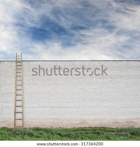 huge white brick wall with a wooden ladder, green grass and cloudy sky background - stock photo