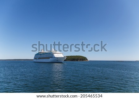 Huge, white, luxury cruise ship anchored in blue water