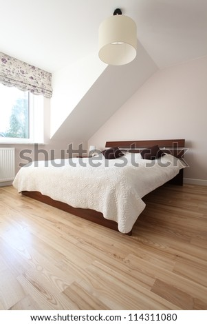 Huge wooden bed in bright spacious bedroom - stock photo