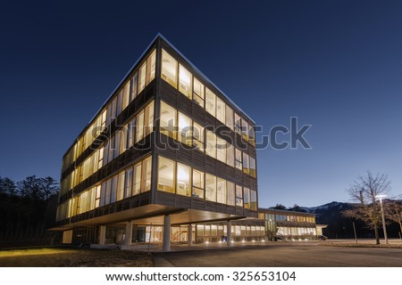 huge wooden timber sustainable office building at dawn - stock photo