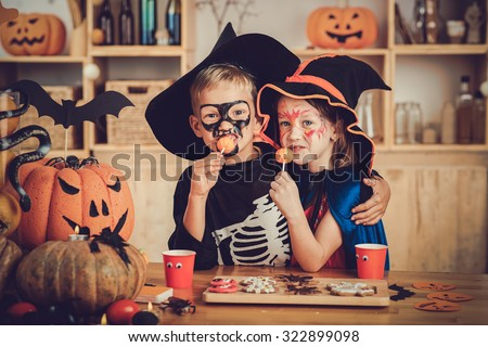 Hugging boy and girl enjoying sweets at Halloween party - stock photo
