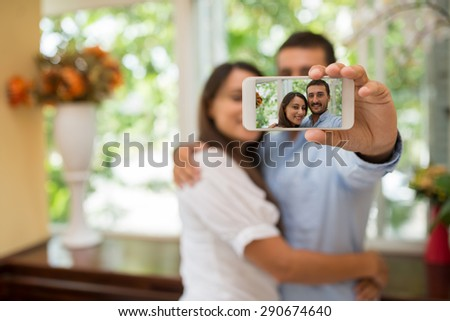 Hugging couple taking selfie, focus on the smartphone screen