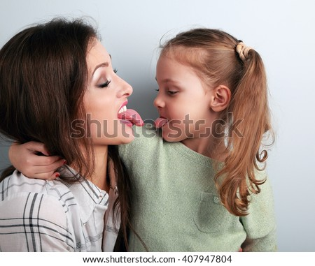 Hugging funny mother and daughter quarreling and showing each other the tongues. Closeup humor portrait - stock photo