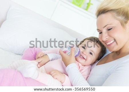 Hugging happy mom and baby, baby drinks a water from a bottle.Shallow doff - stock photo