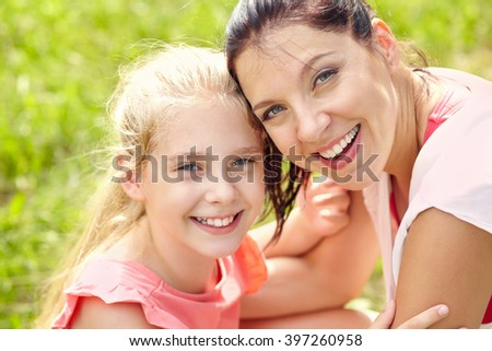hugging happy mother and daughter for a walk in the park