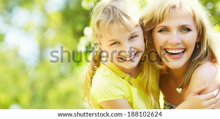 hugging happy mother and daughter for a walk in the park on a light green background. banner