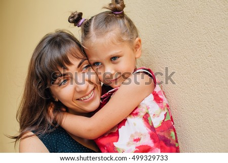 hugging mother and daughter happy together, smiling stylish family. Cute little girl laughing with her mother