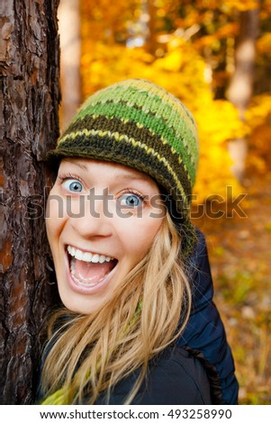 Hugging Tree Trunk in the Woods by Happy Blonde Girl. Woman with Wide Open Eyes and Toothy Smile Looking at Camera over Yellow Autumn Background. Happiness Inspirational Concept Outdoors in Fall.