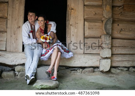 Hugging wedding couple sits on the doorstep