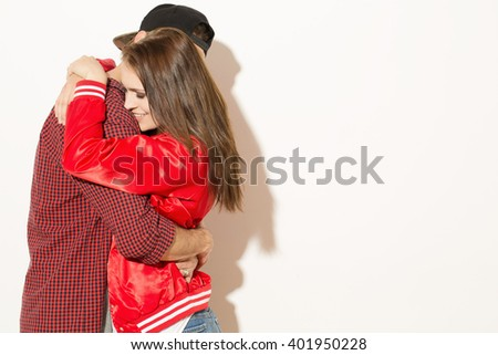 Hugs of love. Attractive hipster female smiling hugging with her boyfriend at the studio copyspace on the side. - stock photo