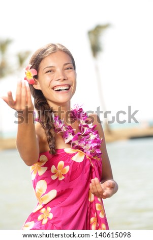 Hula dancer woman dancing hula dance on Hawaii wearing Hawaiian orchid flower lei smiling happy on beach. Travel vacation summer holidays image of beautiful mixed race girl in colorful pink sarong. - stock photo