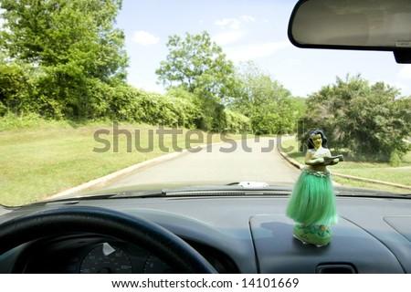 Hula girl on dashboard of car interior. - stock photo