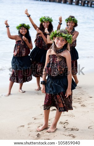 Hula girls on the beach with Hands raised in dance - stock photo