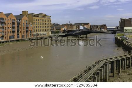 Hull, Humberside, UK. River Hull at low tide with view of Scale Lane swing bridge (open), beached obsolete ship, and flanked by buildings near the estuary, Hull, Humberside, UK.