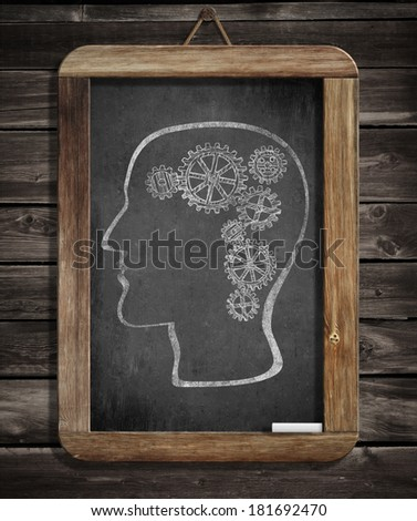 Human brain mechanism with cogs and gears drawn by chalk on blackboard - stock photo
