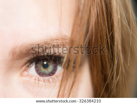 Human eye close-up Beautiful female eye with futuristic lens close up Brown hairs