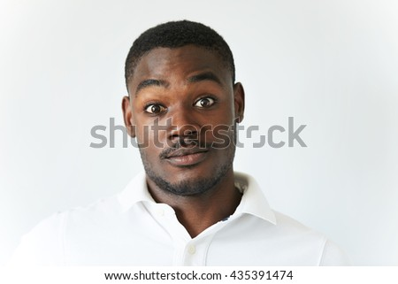 Human face expressions and emotions. Amazed black student or employee in white polo shirt, looking at the camera in disbelief, astonished with unexpected shocking news or sale prices. Body language - stock photo