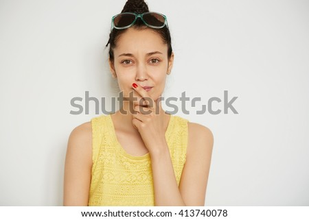 Human face expressions and emotions. Body language. Close up isolated shot of attractive young female with dark hair and brown eyes looking with thoughtful expression at the camera, touching her lips - stock photo