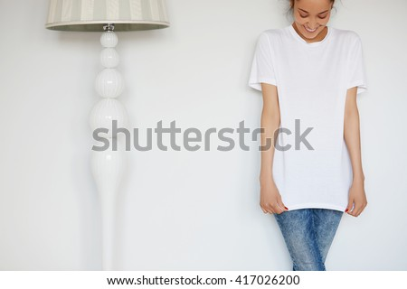 Human face expressions and emotions. Cropped portrait of attractive young female with happy smile posing in white blank copy space T-shirt for your advertising content against white studio wall.  - stock photo