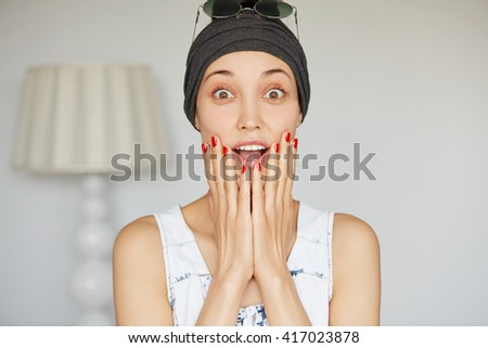 Human face expressions and emotions. Isolated headshot of student girl looking in surprise with hands on her cheeks, mouth wide open. Young woman astonished with some incredible news or sale prices - stock photo