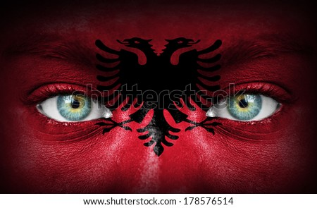 Human face painted with flag of Albania - stock photo