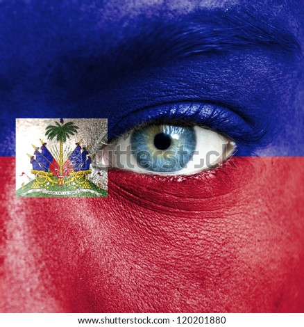 Human face painted with flag of Haiti - stock photo