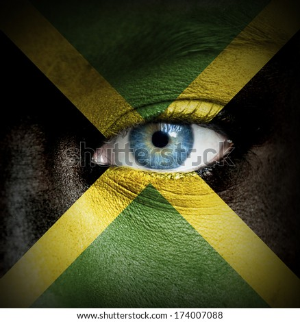 Human face painted with flag of Jamaica - stock photo
