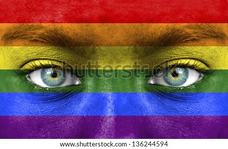 Human face painted with flag of LGBT - stock photo