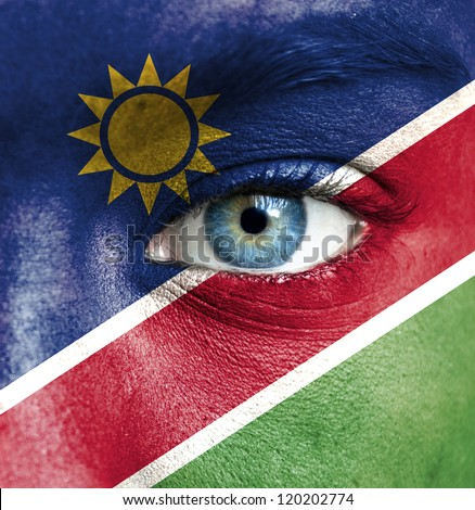 Human face painted with flag of Namibia - stock photo
