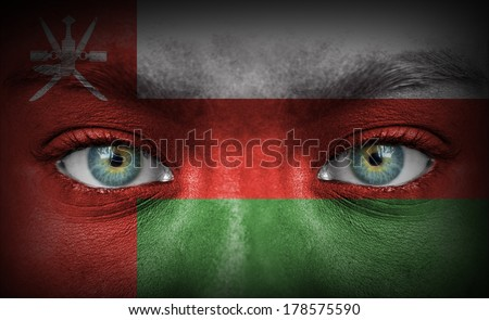 Human face painted with flag of Oman - stock photo