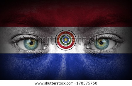 Human face painted with flag of Paraguay - stock photo