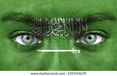 Human face painted with flag of Saudi Arabia - stock photo