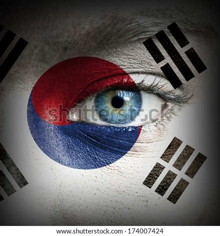 Human face painted with flag of South Korea - stock photo