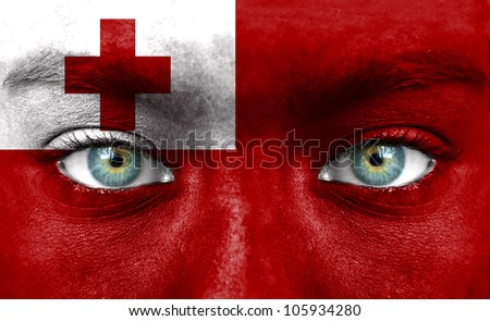 Human face painted with flag of Tonga