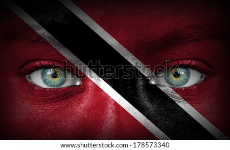 Human face painted with flag of Trinidad and Tobago - stock photo