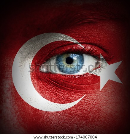 Human face painted with flag of Turkey - stock photo