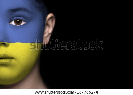 Human face painted with flag of Ukraine - stock photo