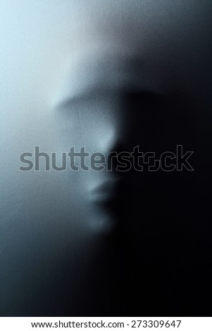 Human face pressing through fabric as horror background