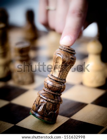 Human finger crashes down king chess piece. - stock photo