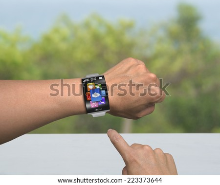 human finger point app icons of smartwatch with bent interface and metal watchband on desk nature background - stock photo
