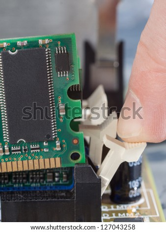 Human finger pushes lever to remove memory module from mother board.