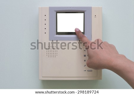 Human finger pushing button of video intercom equipment - stock photo