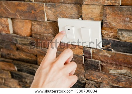Human finger turning off the light switch - green earth and energy saving concept - stock photo