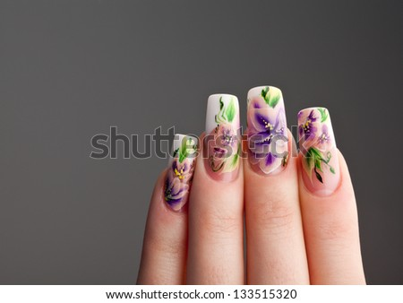Human fingers with beautiful spring manicure over gray background - stock photo