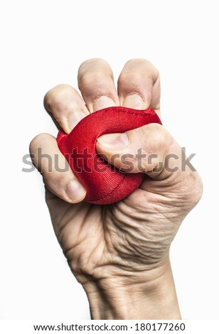 Human fist squeezing red stress ball. Symbol of anxiety, frustration and pressure at work. - stock photo