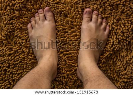 Human foot on brown mat - stock photo