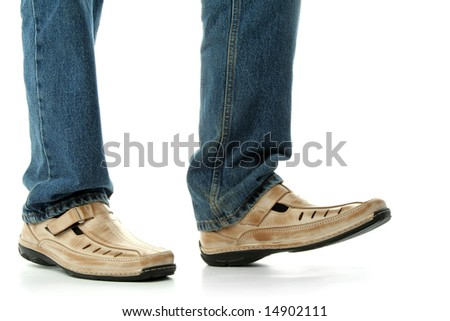 Human foot with brown leather shoes and jeans, isolated on white