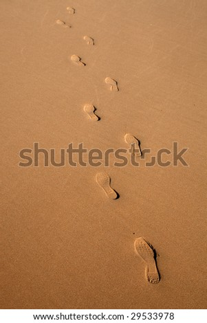 human footprints in the wet sand in a algarve beach - stock photo