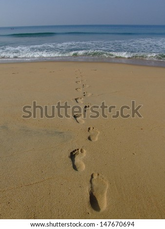 Human footprints leading away from the viewer towards sea. - stock photo