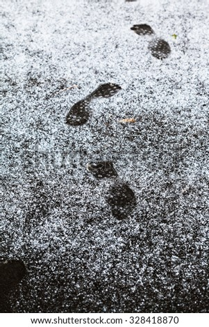 human footprints on sidewalk covered by first snow in autumn - stock photo